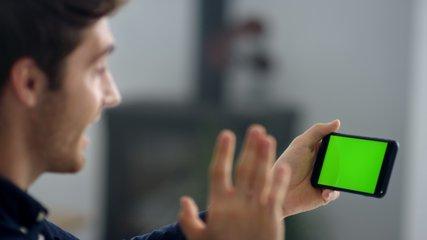 Closeup business man making video call on smartphone in slow motion. Close up of businessman making video chat on green screen mobile phone. Male professional waving hands after conference call.