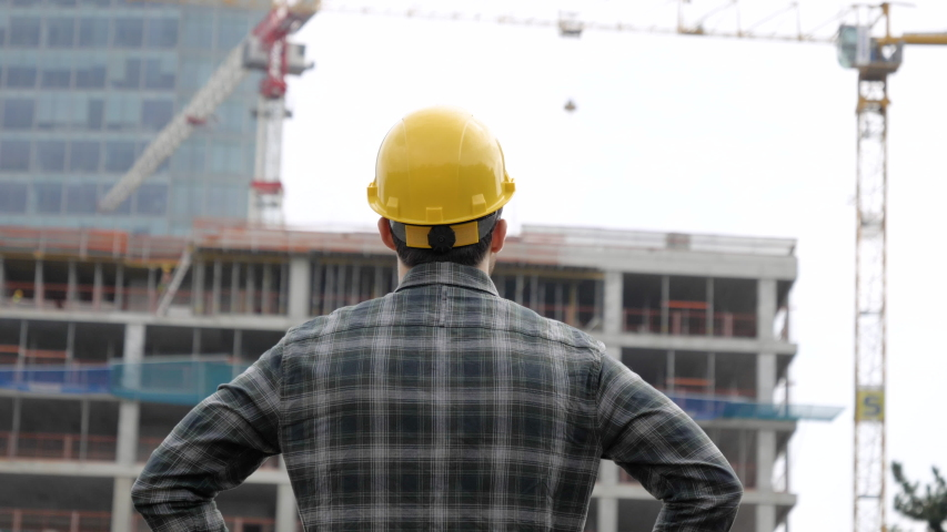 Young engineer looking at construction works.