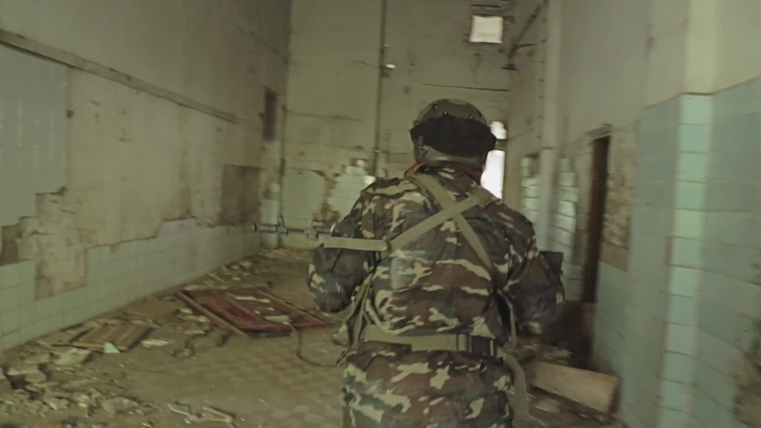 A SWAT team enters the building to storm it. Dynamic motion camera. Armed clashes