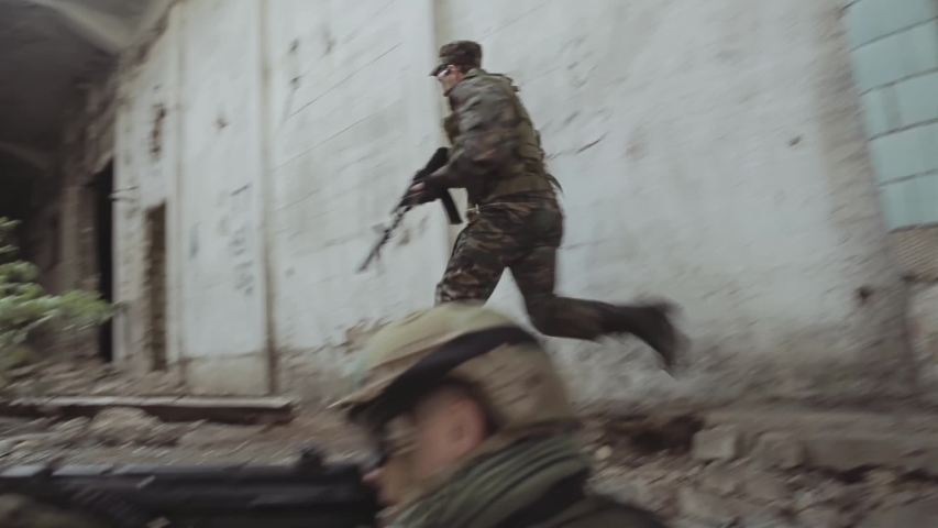 A soldier in a hard hat and with automatic weapons is firing from cover. The soldier gives commands to his partner. Team battle with the enemy