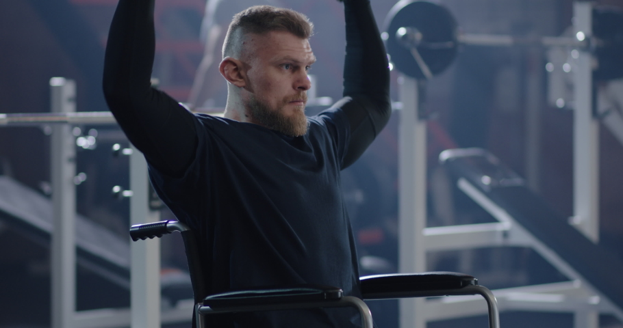Medium shot of wheelchair man lifting weight in gym #1048156756
