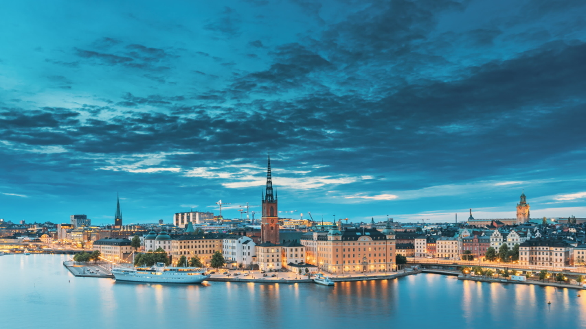Stockholm, Sweden. Scenic View Of Stockholm Skyline At Summer Evening. Famous Popular Destination Scenic Place In Dusk Lights. Riddarholm Church In Day To Night Transition Time Lapse