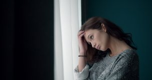 Side view of young thoughtful lady with curly hair dressed casually looking through window at home. Pretty woman feeling loneliness and sadness during leisure time.