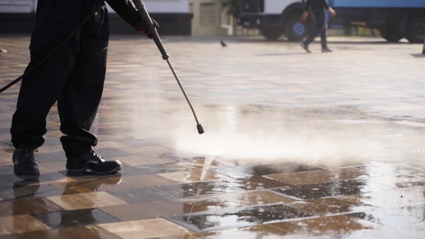 Cleaning city streets with water pressure washer. Janitor sprays city street sidewalk paving slabs. Worker disinfects floor and surfaces from coronavirus. Antibacterial sanitary measures on quarantine | Shutterstock HD Video #1048174951