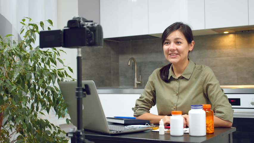 Young woman blogger instructing on proper putting on a medical mask and recording video on camera at home. #1048180735