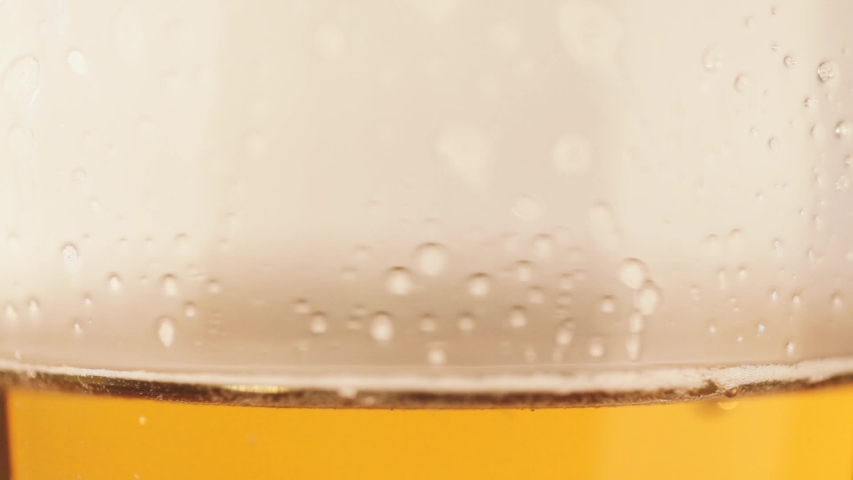 Beer is poured into an almost full glass. a foamy drink is poured from a glass. | Shutterstock HD Video #1048183822
