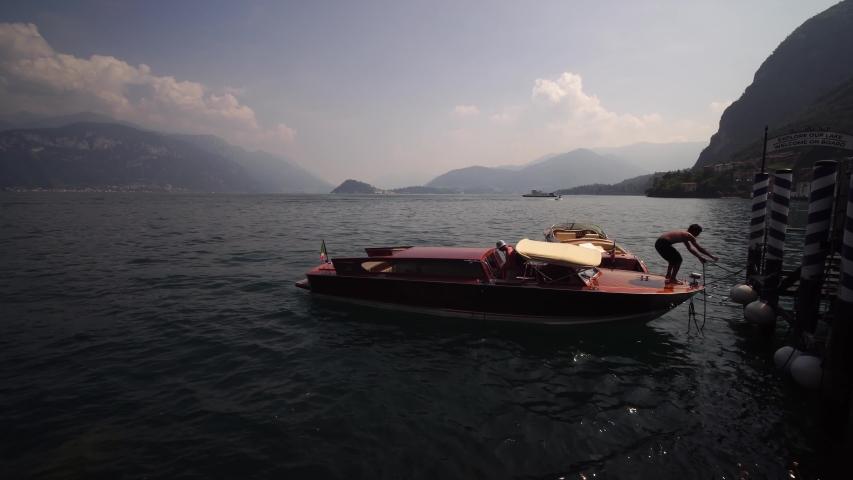 BELLAGIO, LAKE COMO, ITALY - AUGUST 15, 2020: Lake Como, Bellagio. Luxury wooden boat. Summer tourism landmark & romantic honeymoon travel destination in Italy Alps. | Shutterstock HD Video #1048211290