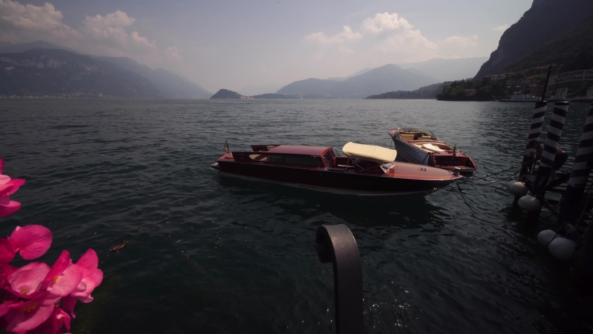 BELLAGIO, LAKE COMO, ITALY - AUGUST 15, 2020: Lake Como, Bellagio. Luxury wooden boat. Summer tourism landmark & romantic honeymoon travel destination in Italy Alps. | Shutterstock HD Video #1048211293