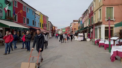 BURANO (VE), ITALY - FEBRUARY 21, 2020: tourists walking along the colorful houses of the ancient fishing village. Hyperlapse shot