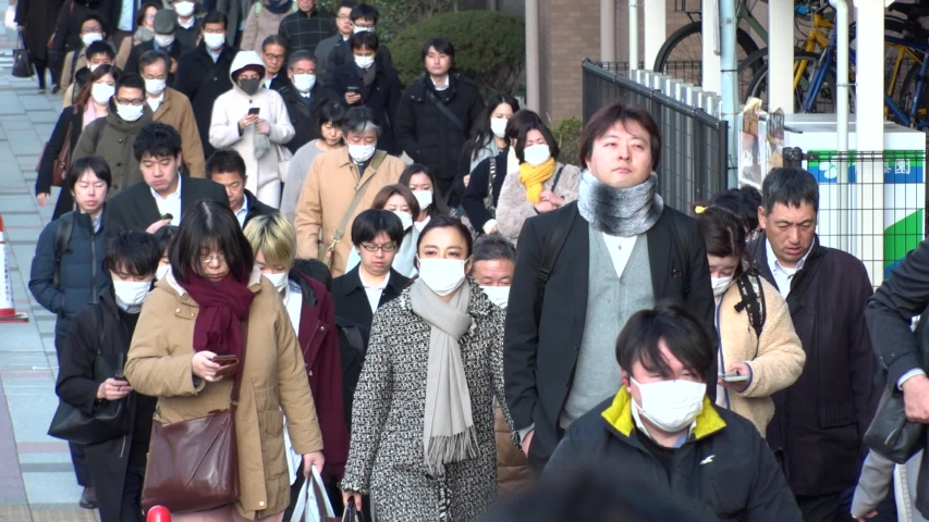 TOKYO, JAPAN - MARCH 2020 : Crowd of people walking down the street in morning rush hour. Many commuters going to work. People wearing mask to protect from Coronavirus(COVID-19) or cold. Slow motion.