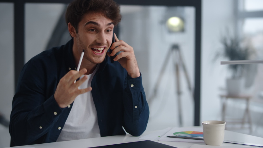 Closeup cheerful businessman talking mobile phone emotionally at home office. Positive entrepreneur supporting client on smartphone in slow motion. Happy business man finishing phone call indoor. Royalty-Free Stock Footage #1048219321