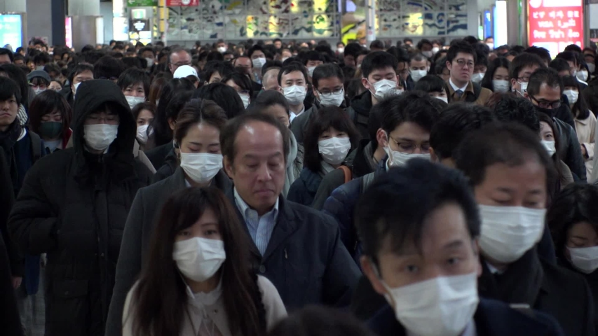 TOKYO, JAPAN -MARCH 2020 : Crowd of people walking at Shinagawa station in busy morning rush hour. Many commuters going to work. People wearing mask to protect from Coronavirus(COVID-19). Slow motion.