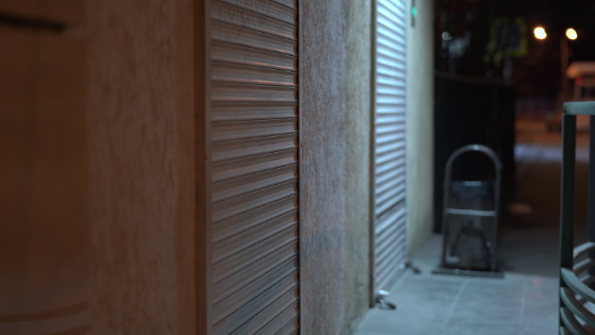 Empty night city street, roller shutters at closed shop door. | Shutterstock HD Video #1048231909