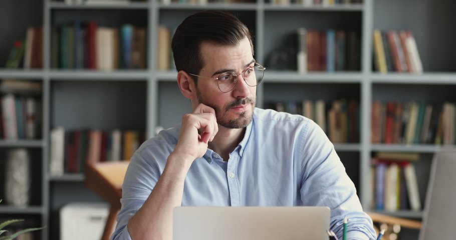 Thoughtful business man thinking of problem solution working on laptop. Serious doubtful male professional looking away at laptop considering market risks, making difficult decision sitting at desk | Shutterstock HD Video #1048239448