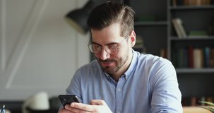 Smiling young man using smartphone indoors. Millennial businessman mobile technology user working in digital applications gadget searching information online, texting messages at home or in office.