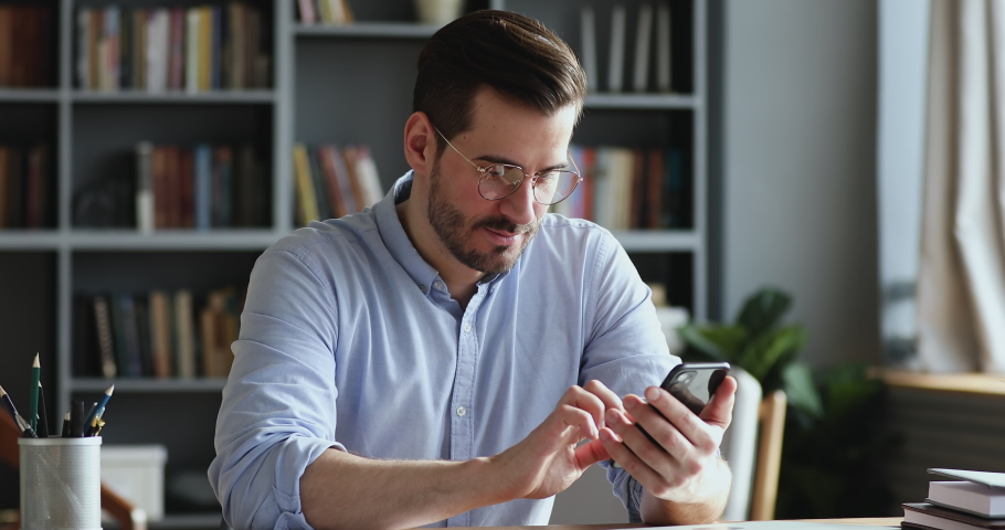 Male millennial professional holding modern smartphone texting message in office. Young businessman using helpful mobile apps for business time management organization concept sitting at work desk.