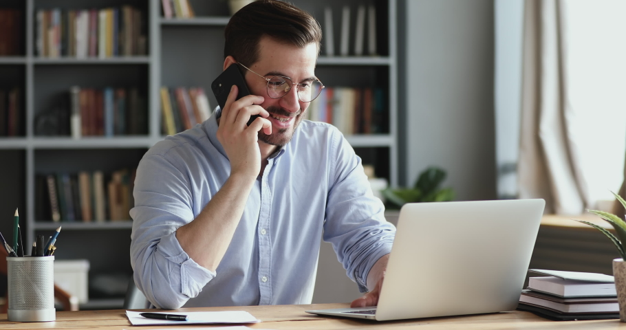 Smiling business man using laptop talking on cell phone sits at desk. Happy confident male professional manager web designer consulting client about online project making business call at workplace.