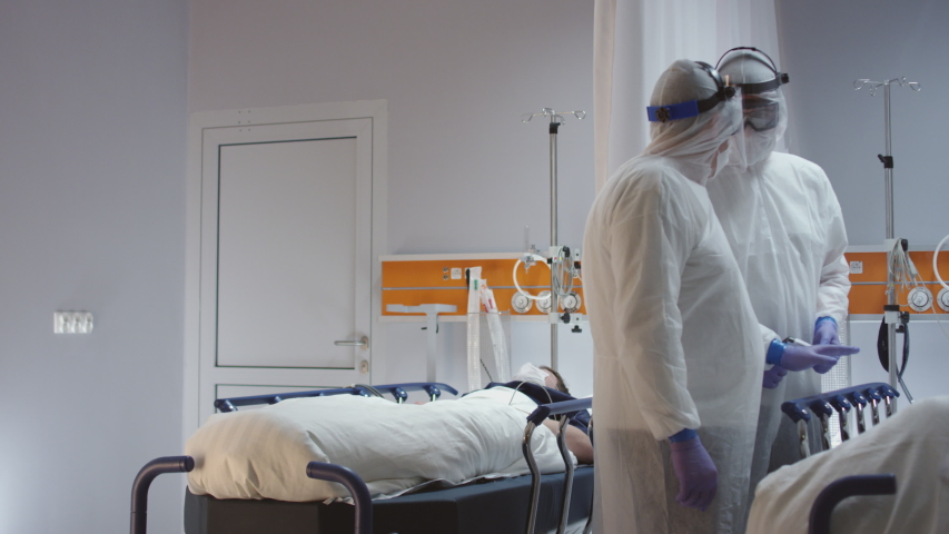 Doctor in Orange Protective Suit Turning On Coronavirus Pateint's Heart Monitor - Wide Dolly Shot in Slow Motion | Shutterstock HD Video #1048243291