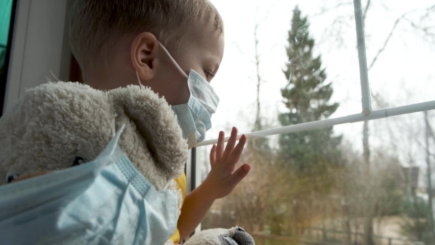 Quarantine, threat of coronavirus. Sad child and his teddy bear both in protective medical masks sits on windowsill and looks out window. Virus protection, pandemic, prevention epidemic.