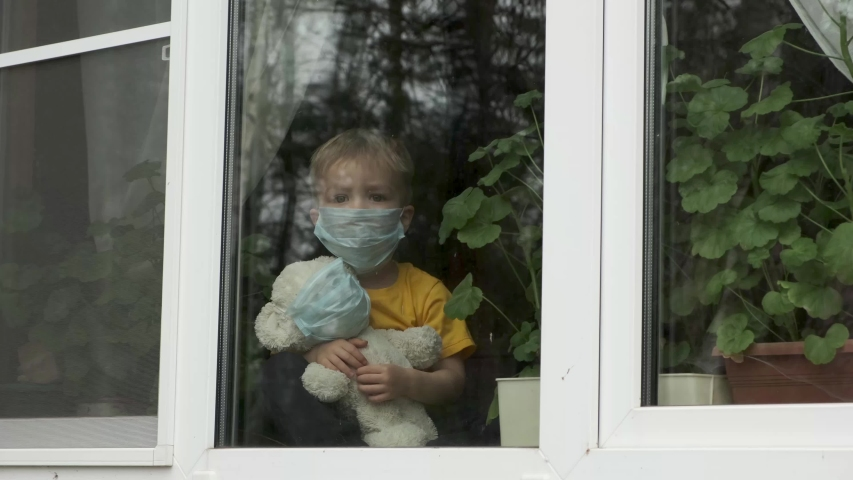 Stay at home quarantine coronavirus pandemic prevention. Sick child with teddy bear in protective medical masks sits on windowsill and looks out window. View from street. Prevention epidemic. Royalty-Free Stock Footage #1048244101