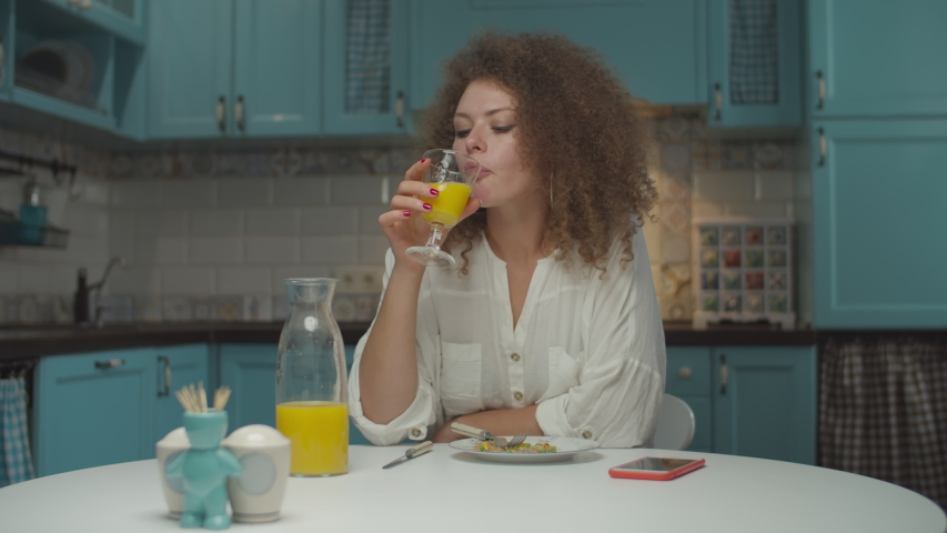 Young 20s curly hair woman eating meal alone on the kitchen. Female eating dinner and drinking orange juice at home.