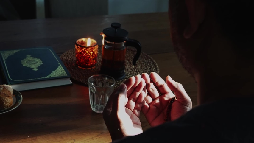 Fasting during Ramadan. Breaking the fast.Religious Muslim man praying to God.Muslim will breaking their fasting after sundown with date following the tradition of Muhammad with water or tea Royalty-Free Stock Footage #1048249399