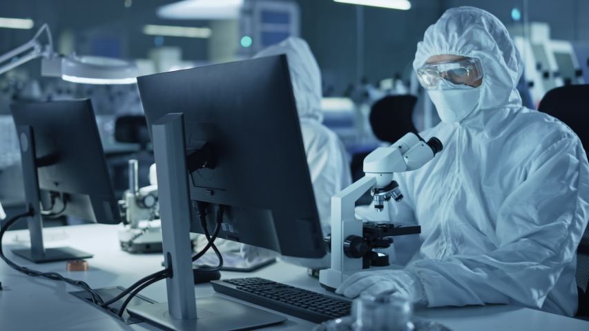 Research Factory Cleanroom: Engineers / Scientists wearing Coveralls and Gloves Use Microscopes to Inspect Motherboard Microprocessor Components, Developing High Tech Modern Electronics Royalty-Free Stock Footage #1048253779