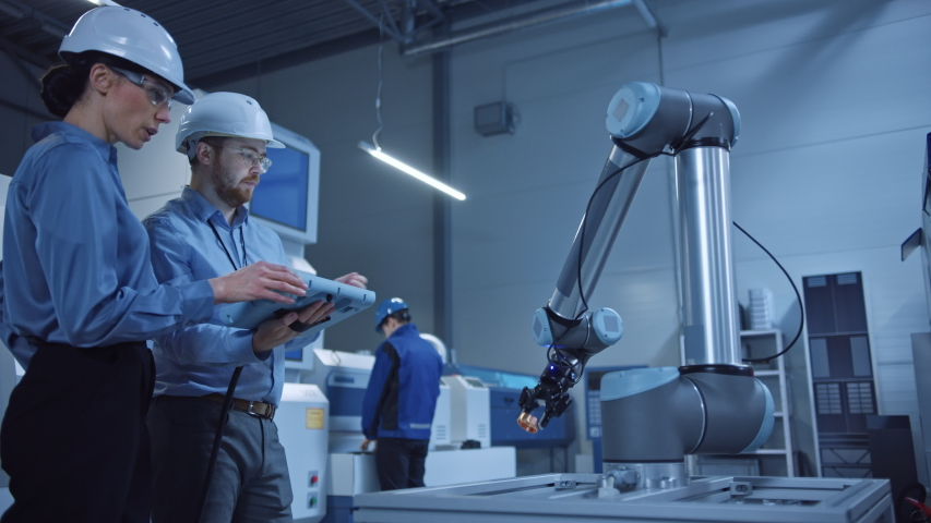 Factory Workshop: Professional Female Engineer and Male Machinery Operator Use Industrial Digital Tablet Computer to Work and Program Robot Arm for Production Line. Tech Facility with CNC Machines Royalty-Free Stock Footage #1048253845