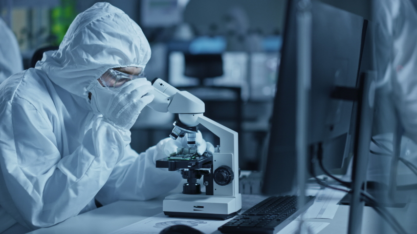 Research Factory Cleanroom: Engineer / Scientist wearing Coverall and Gloves Uses Microscope to Inspect Samples, Developing High Tech Modern Technology for Medical, High Precision Electronics Industry Royalty-Free Stock Footage #1048253959