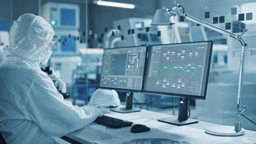 Electronics Factory Cleanroom: Engineer / Scientist in Coveralls Wors on Computer, Screen Shows Infographics and Software System Control UI, Developing Electronics for Medical Electronics Royalty-Free Stock Footage #1048253980