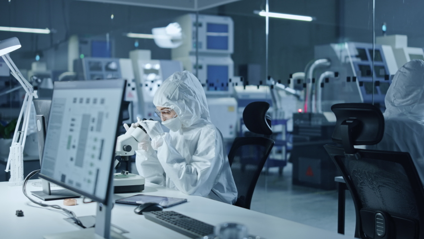 Research Factory Cleanroom: Team of Engineers and Scientists in Coveralls Work on Computers, Use Microscope to Inspect Motherboard Microprocessor, Developing Electronics for Medical Electronics Royalty-Free Stock Footage #1048253983