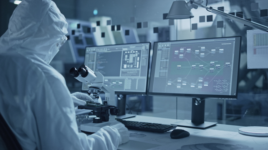 Research Factory Cleanroom: Team of Engineers and Scientists in Coveralls Work on Computers, Use Microscope to Inspect Motherboard Microprocessor, Developing Electronics for Medical Electronics Royalty-Free Stock Footage #1048253995