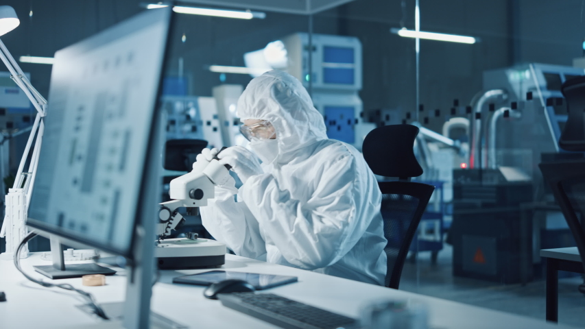 Modern Factory: Team of Engineers and Scientists in Clean Sterile Coveralls Work on Desktop Computers, Use Microscope, Developing Solutions for High-Tech Medical Vaccine Research