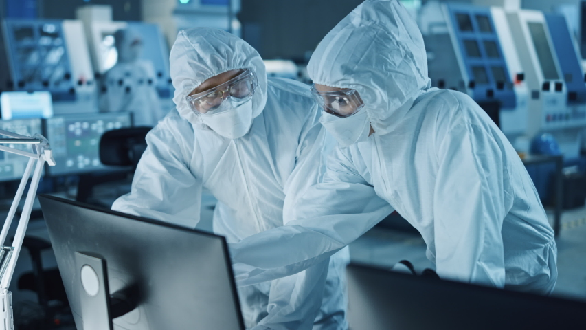 Research Factory Cleanroom: Engineer and Scientist Wearing Coveralls Talk and Work on Computer, Use Microscope to Inspect Motherboard Microprocessor, Develop Electronics for Medical Electronics Royalty-Free Stock Footage #1048254004