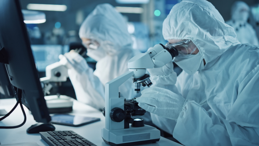 Research Factory Cleanroom: Engineers / Scientists wearing Coveralls and Gloves Use Microscopes to Inspect Motherboard Microprocessor Components, Developing High Tech Modern Electronics Royalty-Free Stock Footage #1048254010