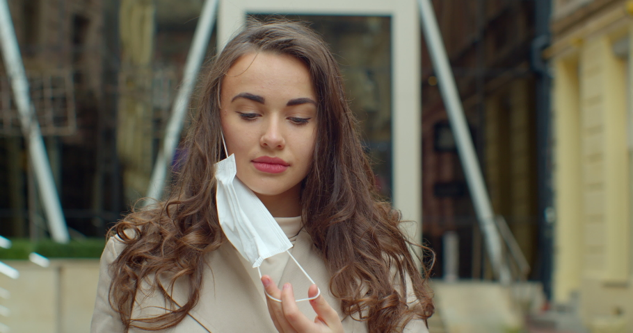Portrait of a young student woman wearing protective mask on street.Concept of health and safety life, N1H1 coronavirus, virus protection. | Shutterstock HD Video #1048259119