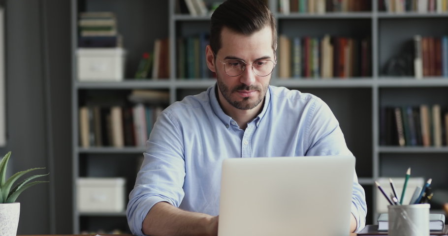 Focused business man working on laptop computer making notes sitting at home office desk. Young adult male professional manager doing marketing research writing checklist on paper at workplace. Royalty-Free Stock Footage #1048261150