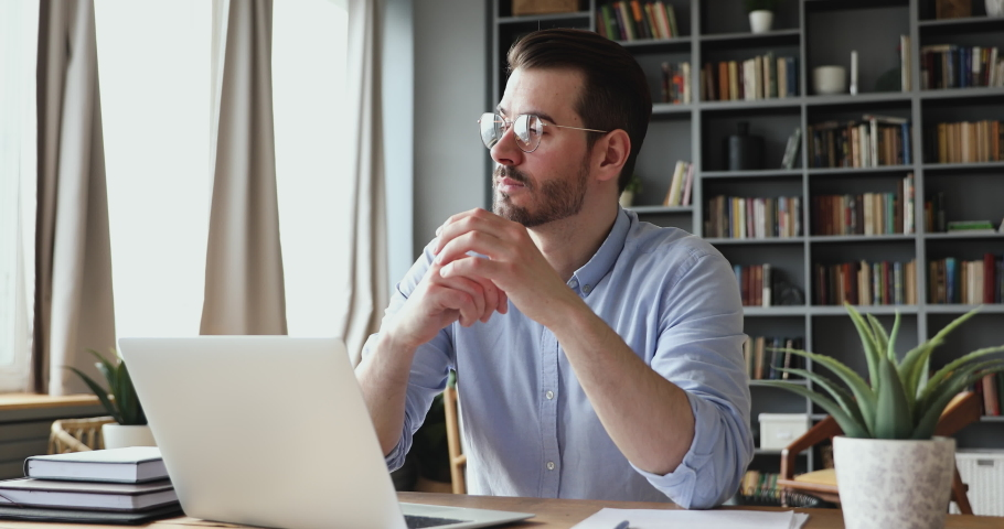 Concentrated serious businessman thinking of problem solution working on laptop. Thoughtful male programmer market analyst or software developer considering risks using computer sitting at workplace. Royalty-Free Stock Footage #1048261153