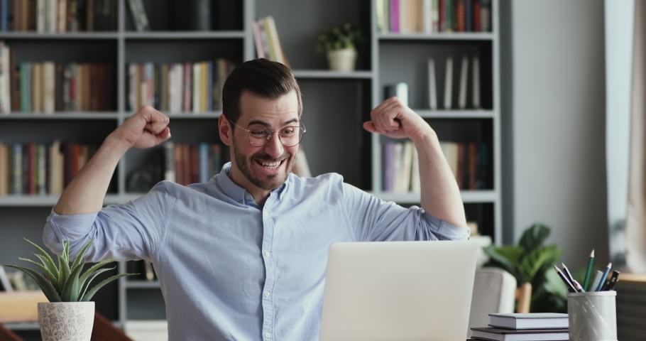 Excited business man checking email reading great news on laptop. Amazed male professional winner feeling happy receiving new job opportunity, reward bonus, celebrates financial market growth concept.