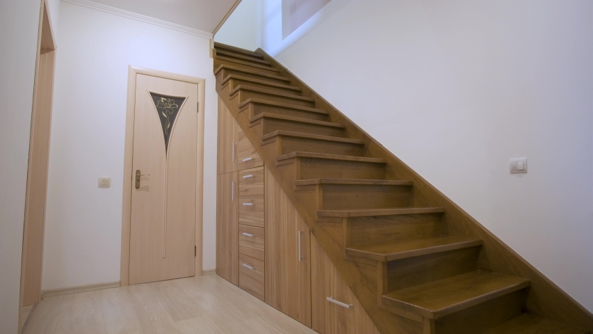 Kyiv, Ukraine - August 7, 2019: Modern architecture interior with luxury hallway with glossy wooden stairs in multi-storey house. Custom built pullout cabinets on glides in slots under stairs.