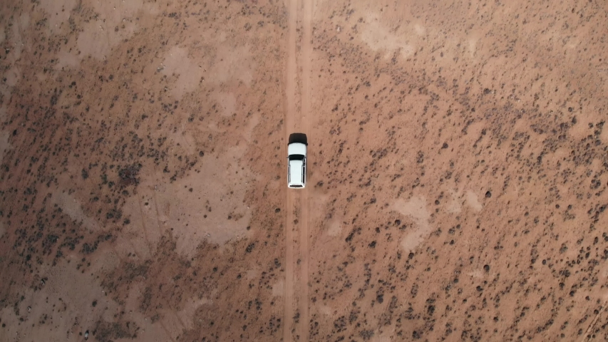Aerial over off road 4x4 car driving along gravel trail path. Overhead on white offroad vehicle on desert Pamir Highway silk road travelling in Tajikistan,Asia. 4k drone flight.Top view perspective | Shutterstock HD Video #1048264366