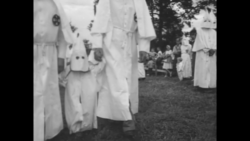 CIRCA 1920s - At a racist KKK rally in Stone Mountain, Georgia, the American flag is honored and children are present.