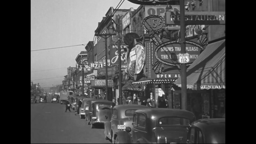 CIRCA 1938 - Footage is shot from a car as it drives past shops, restaurants, and movie theaters on a city street.