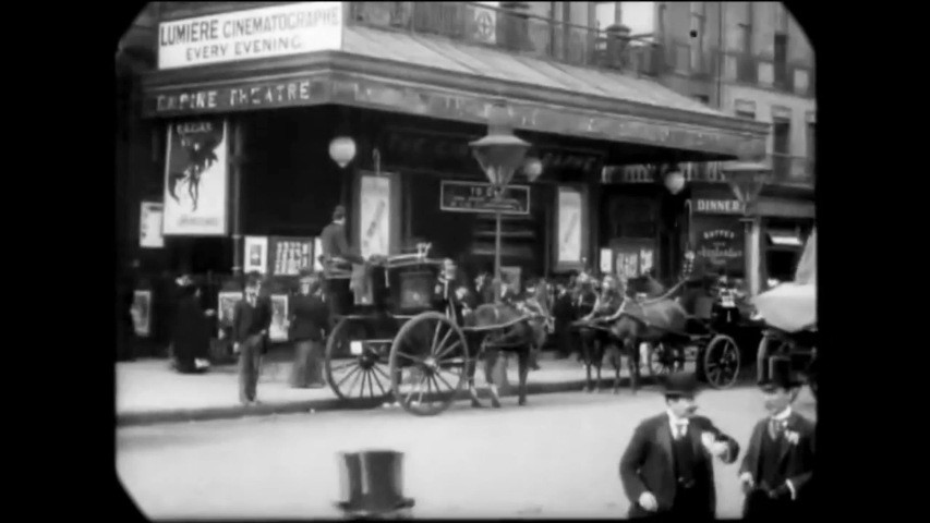 CIRCA 1896 - People come in and out of a movie theater in Leicester Square, London, which is showing French films.