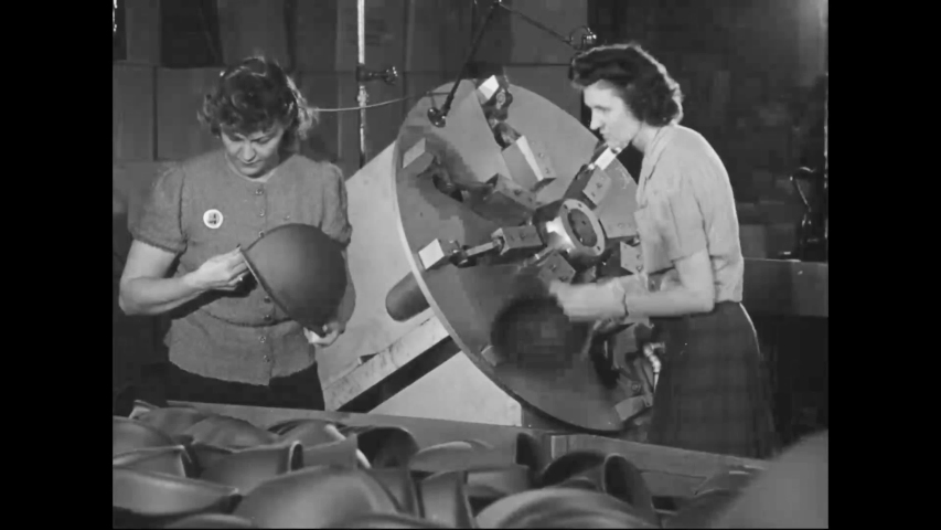 CIRCA 1940s - Women make and inspect helmets at an army world war two war factory.