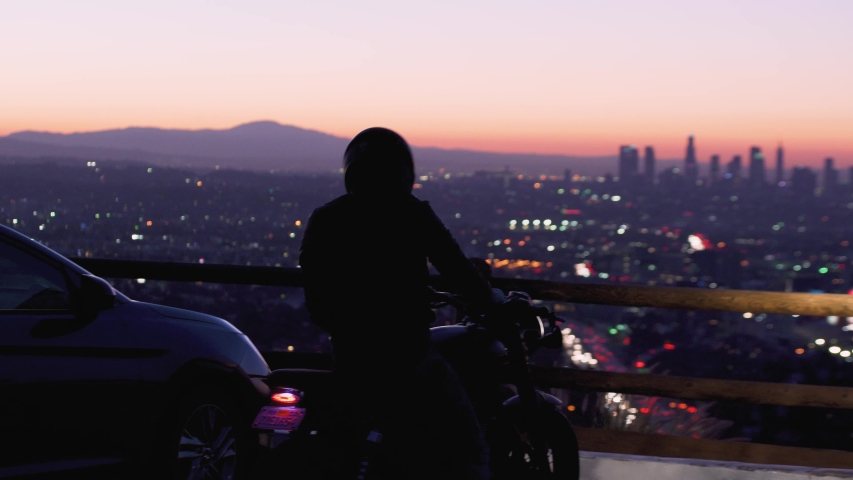 Los Angels city skyline at night view from viewpoint. Illuminated city view in the evening. Silhouette of a biker at sunset. Man enjoying city skyline. Freedom, destination, adventure concept. | Shutterstock HD Video #1048277368