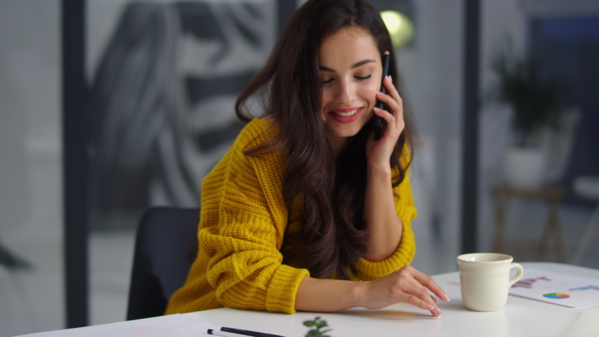 Portrait of smiling businesswoman talking mobile phone in office. Happy girl speaking cellphone at workplace in slow motion. Close up of relaxed business woman calling phone indoor.