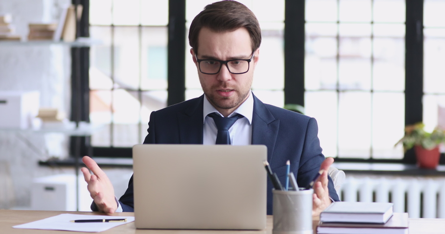 Angry stressed businessman wearing suit feeling mad about broken stuck laptop. Frustrated executive using computer outraged by financial market crash concept reads bad online news sits at office desk.