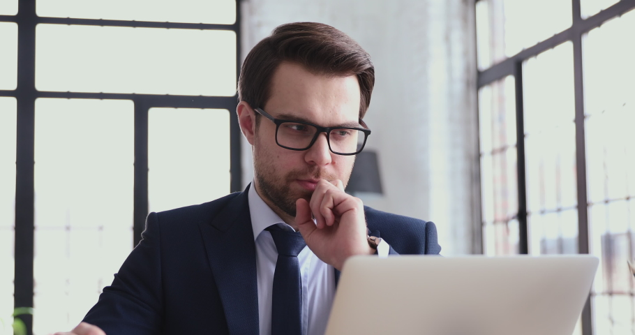 Serious male executive investor analyst reviewing online market thinking of financial forecast. Thoughtful smart businessman works on laptop watching webinar, makes notes, considering business ideas. Royalty-Free Stock Footage #1048281571