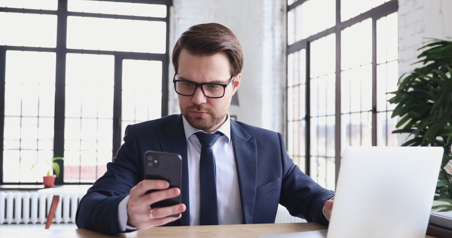 Serious businessman using laptop computer and modern smartphone in office. Smart executive multitasking checking synced apps at work. Mobile and pc technology data synchronization for business concept Royalty-Free Stock Footage #1048283101